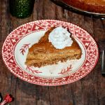 red and white plate with a slice of spice cake garnished with a dallop of whipped cream
