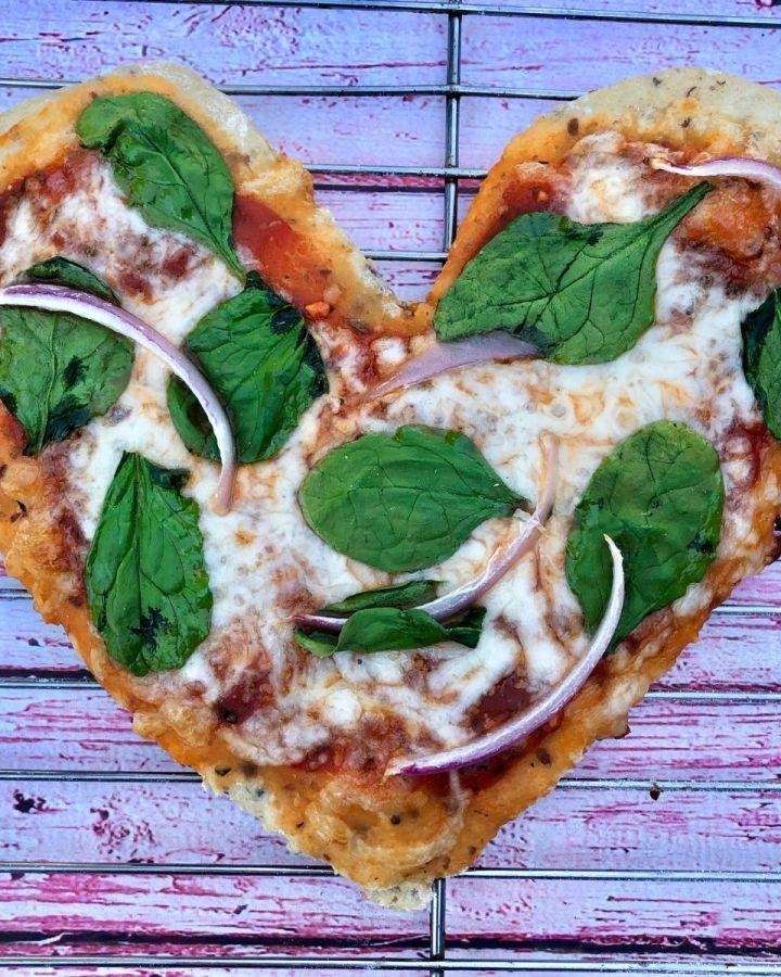 Homemade heart shaped pizza with spinach and red onion on wire rack over pink wooden background