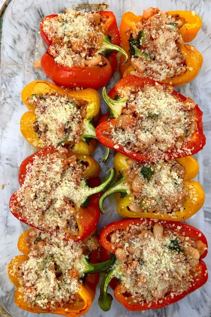 red, yellow, and orange stuffed peppers sprinkled with parmesan cheese