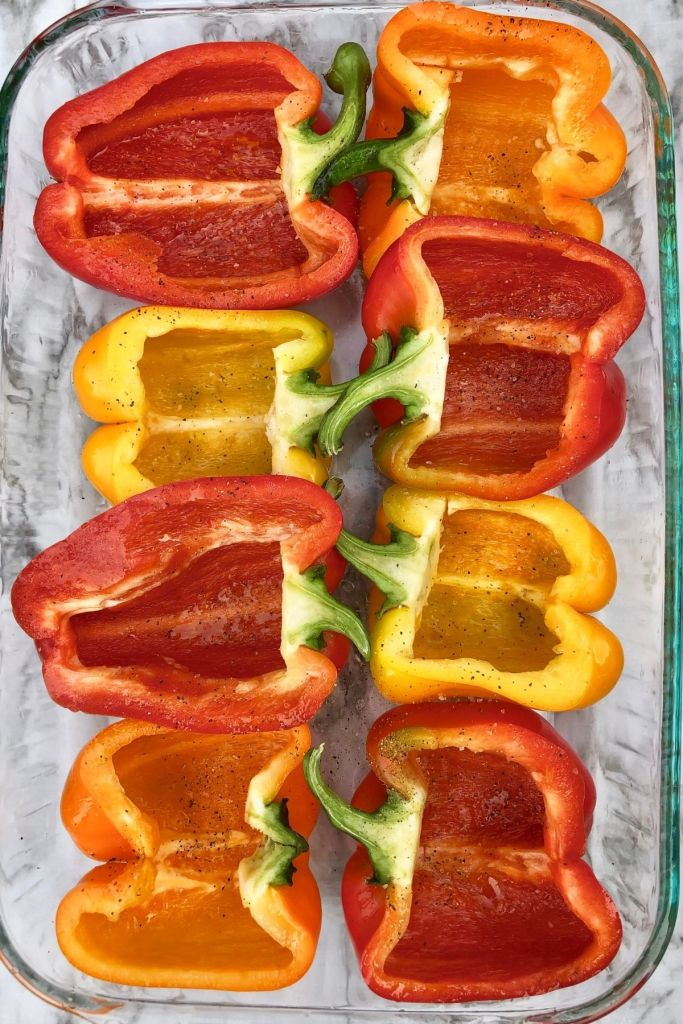 halved red, yellow, and orange peppers in a 9x13 pyrex glass dish