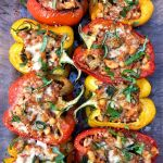 red, yellow, and orange stuffed peppers garnished with fresh basil