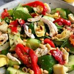 Mediterranean Chicken Salad with greens, chicken, roasted red peppers, artichoke hearts, cucumbers, and toasted pine nuts