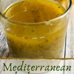 A glass filled with yellow colored Mediterranean Salad Dressing