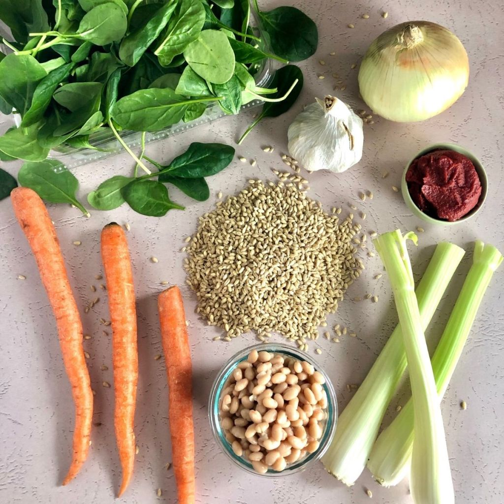 fresh spinach, 3 carrots, 3 celery, an onion, garlic, tomato paste, navy beans, and barley on light pink background