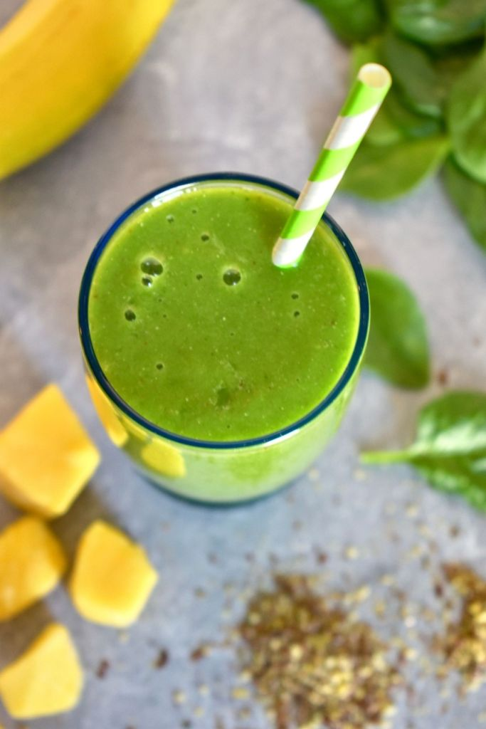 Glass of green smoothie with green and white striped straw surrounded by whole banana, flaxseed, mango chunks, and spinach leaves