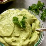 bowl of avocado sauce garnished with fresh cilantro