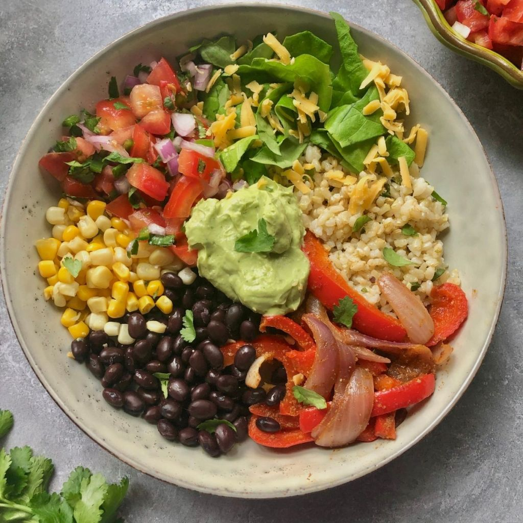 bowl of cilantro lime rice, pico de gallo, lettuce, cheese, corn, black beans, grilled onions & peppers, avocado sauce and garnished with fresh cilantro