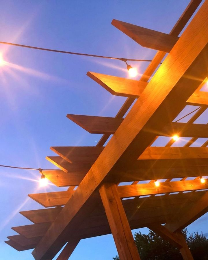 wooden arbor with twinkly lights and purplish blue sky at night