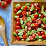 sliced tomato and cucumber salad garnished with dill in a brown wooden bowl