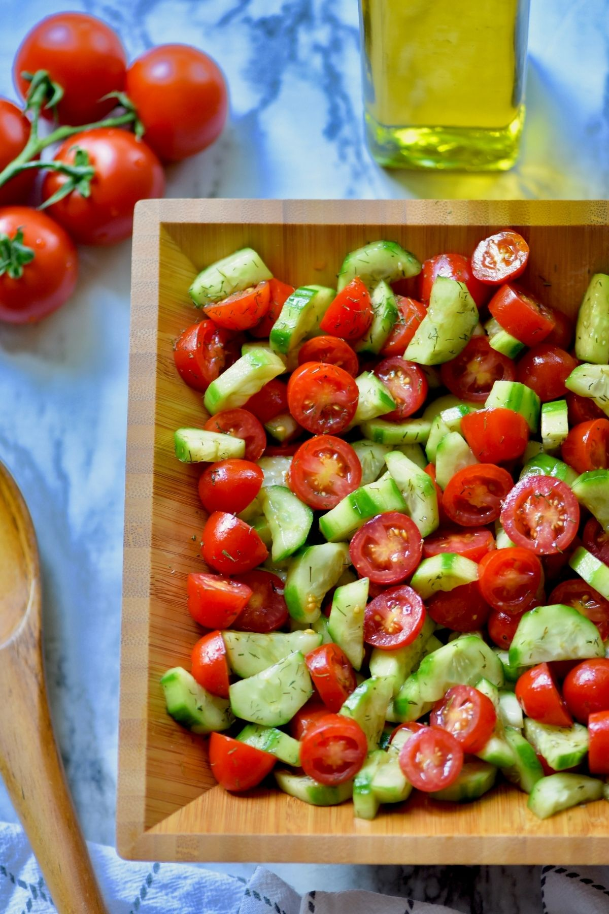 sliced tomato and cucumber salad mixed with balsamic vinegar and dill in a brown wooden bowl