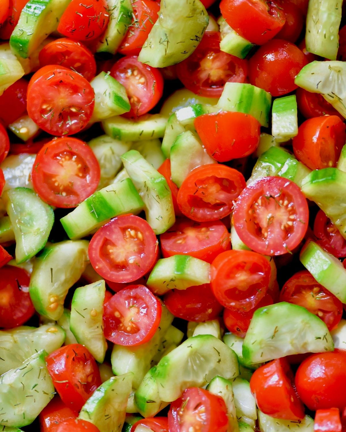 close up shot of sliced cucumbers and tomatoes coated in balsamic vinegar and garnished with fresh dill
