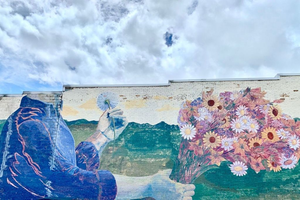 mural of a man in blue shirt with no head (it's in the clouds) holding a bouquet of flowers
