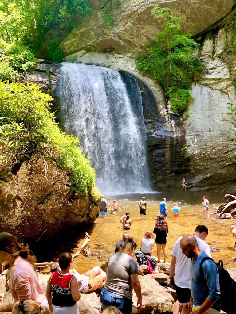 waterfall surrounded by rock and trees on a sunny day with people wading in the shallow stream below