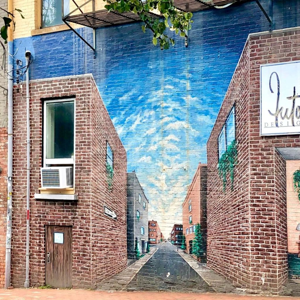 mural of a 3D street on the side of a brick building