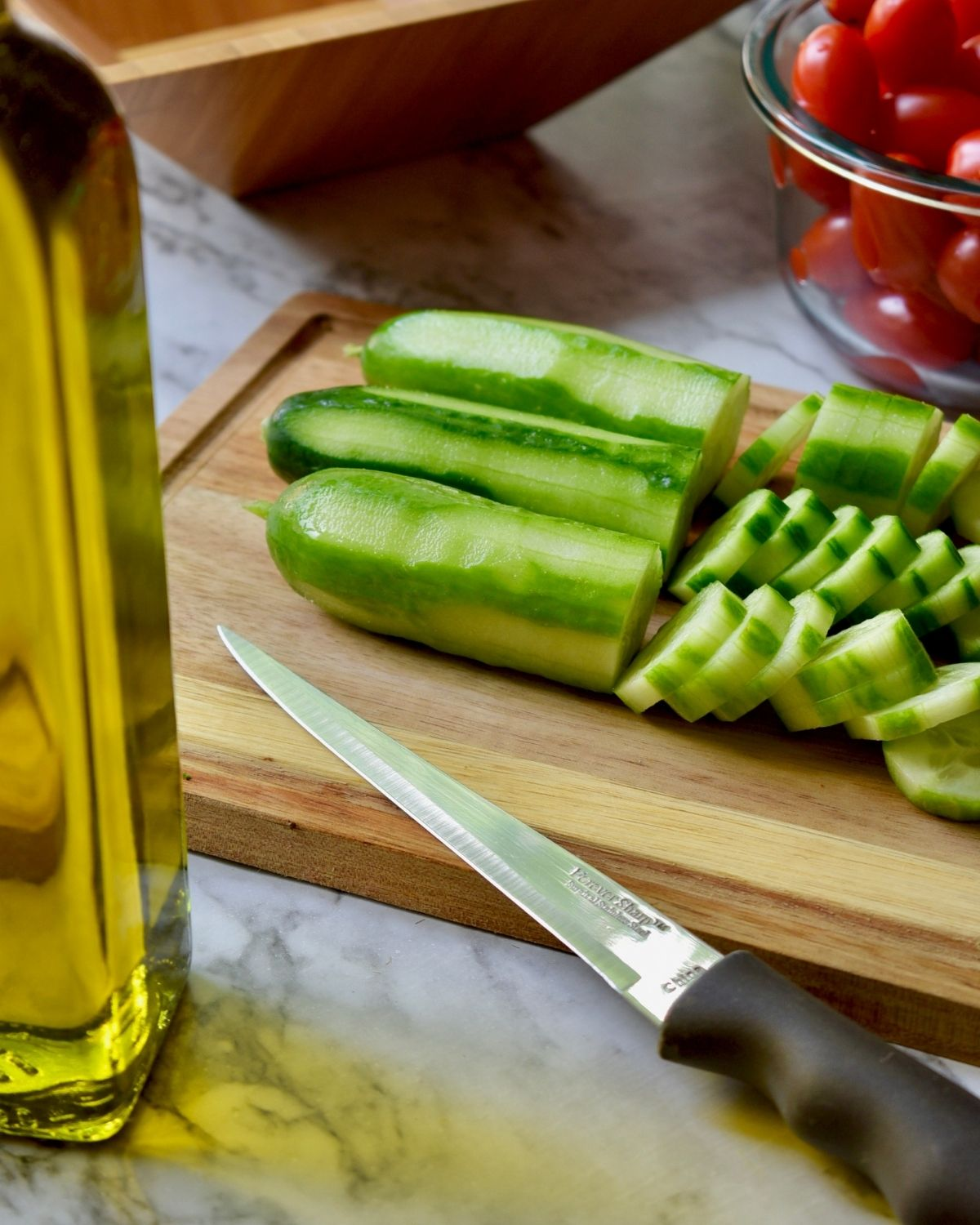 miniature cucumbers peeled into stripes and then sliced on a wooden cutting board  next to a bowl of tomatoes with a container of olive oil on the counter