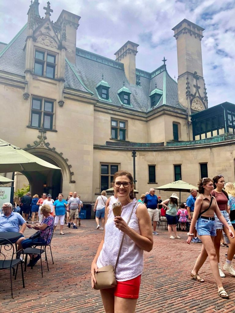woman holding an ice cream cone in front of the Biltmore Castle with people walking around