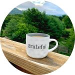 coffee mug with the word grateful on it sitting on a wooden beam with the North Carolina mountains in the background