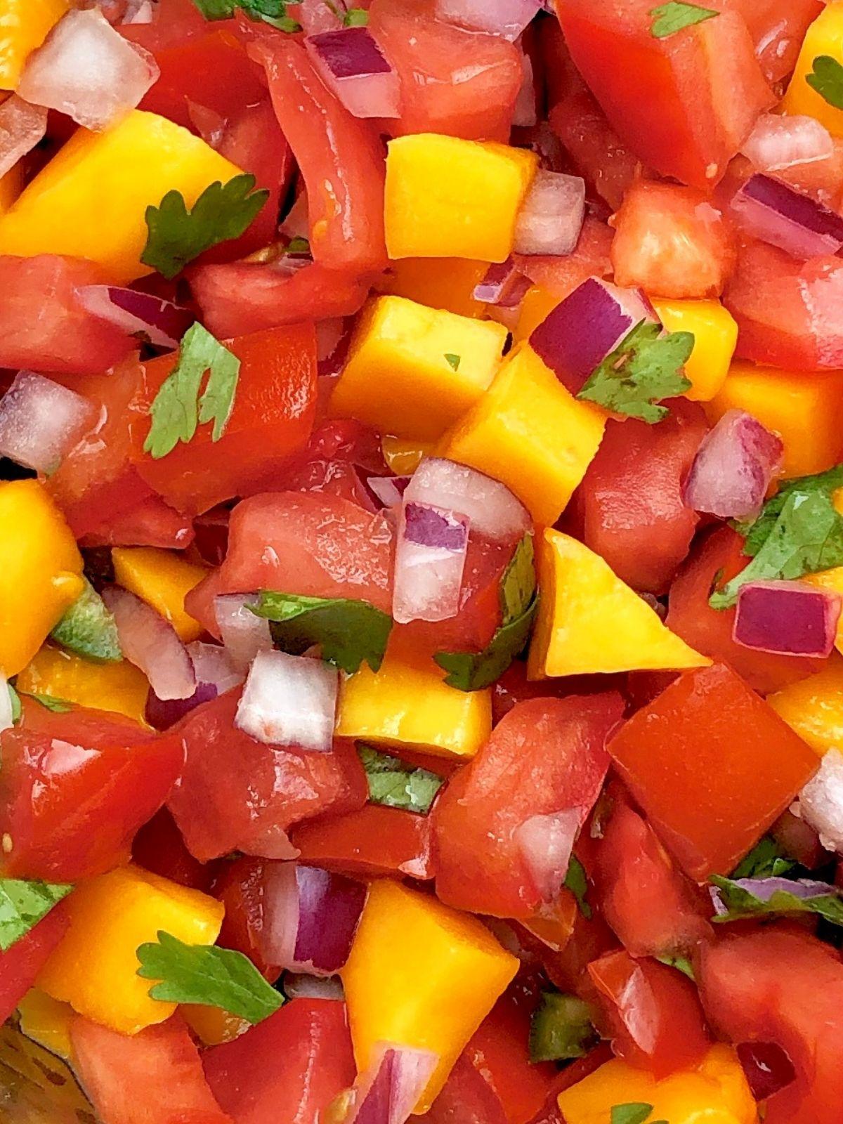 close-up of mango pico de gallo made with fresh tomato, red onion, and cilantro
