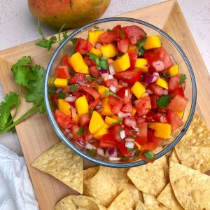 bowl of Mango Pico De Gallo on a wooden platter garnished with tortilla chips, fresh cilantro with a fresh mango off to the side
