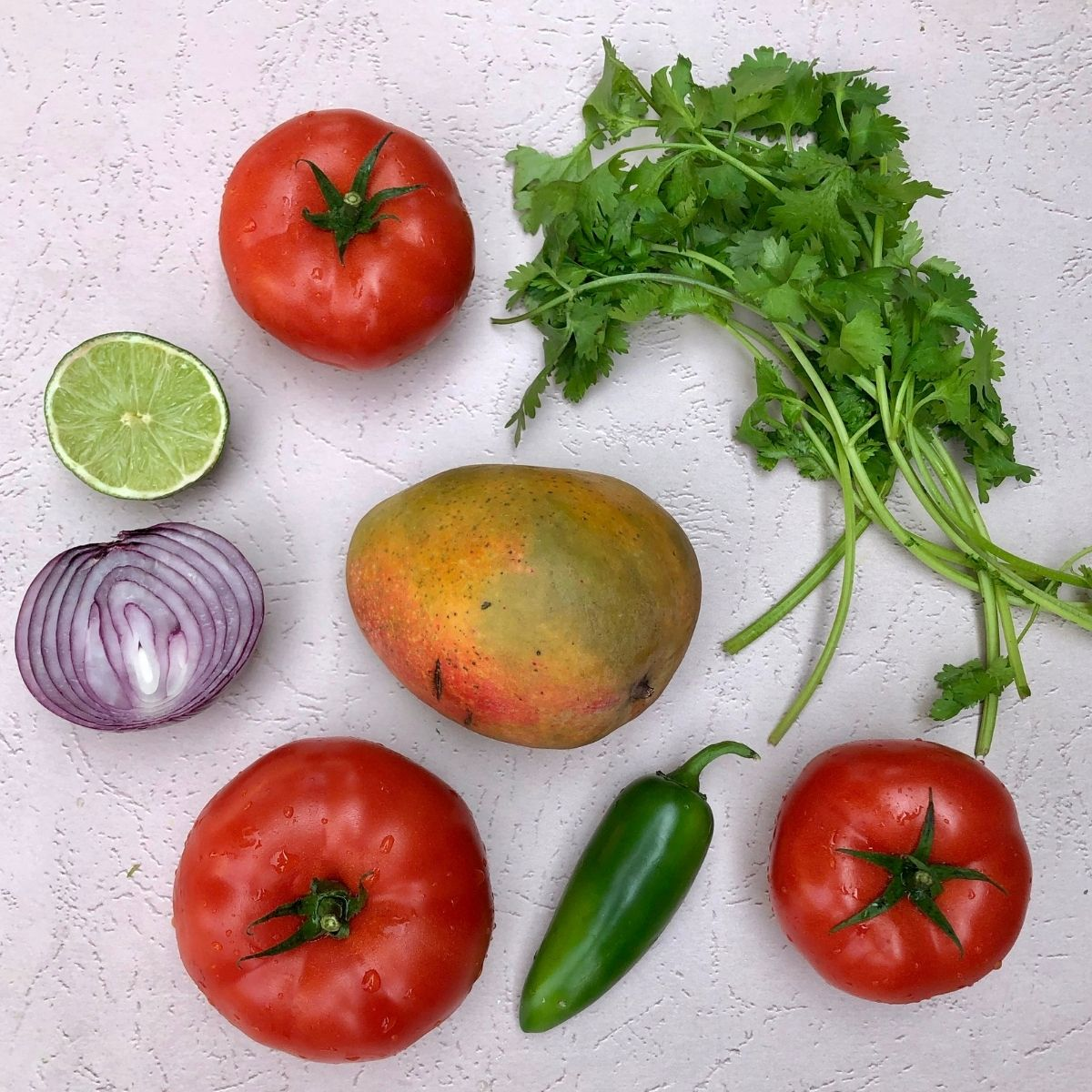 3 fresh tomatoes, 1 fresh mango, 1 jalapeno, 1/2 red onion, lime, bunch of cilantro spread out on a light pink backdrop