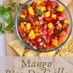 a bowl of fresh mango pico de gallo on a wooden platter garnished with tortilla chips and fresh cilantro