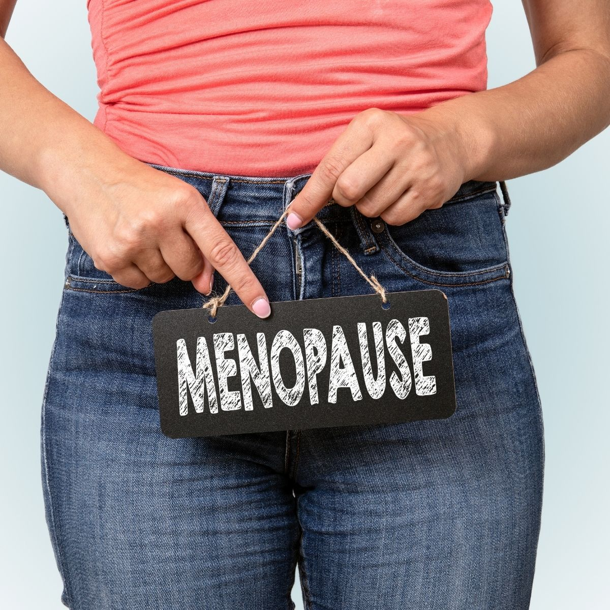 women is jeans and pink tip pointing to a sign she is holding that states menopause