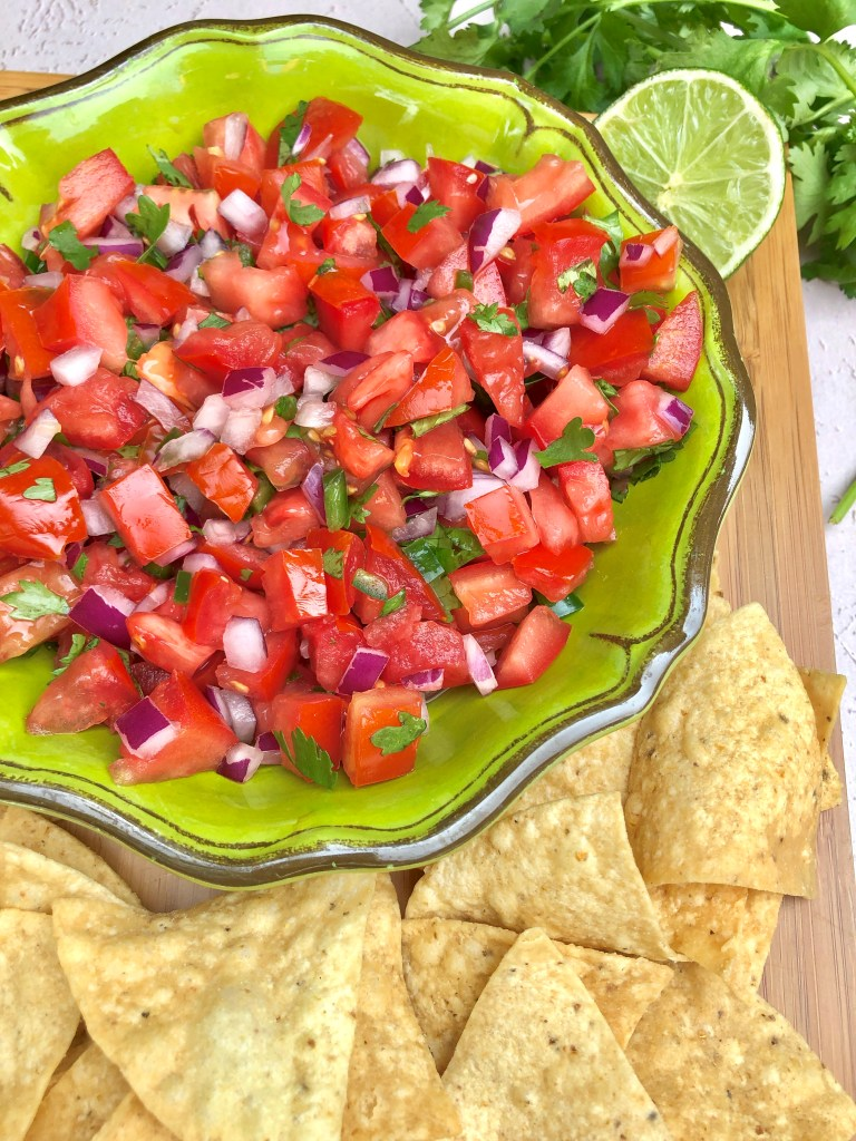 green bowl of pico de gallo on brown platter with tortilla chips