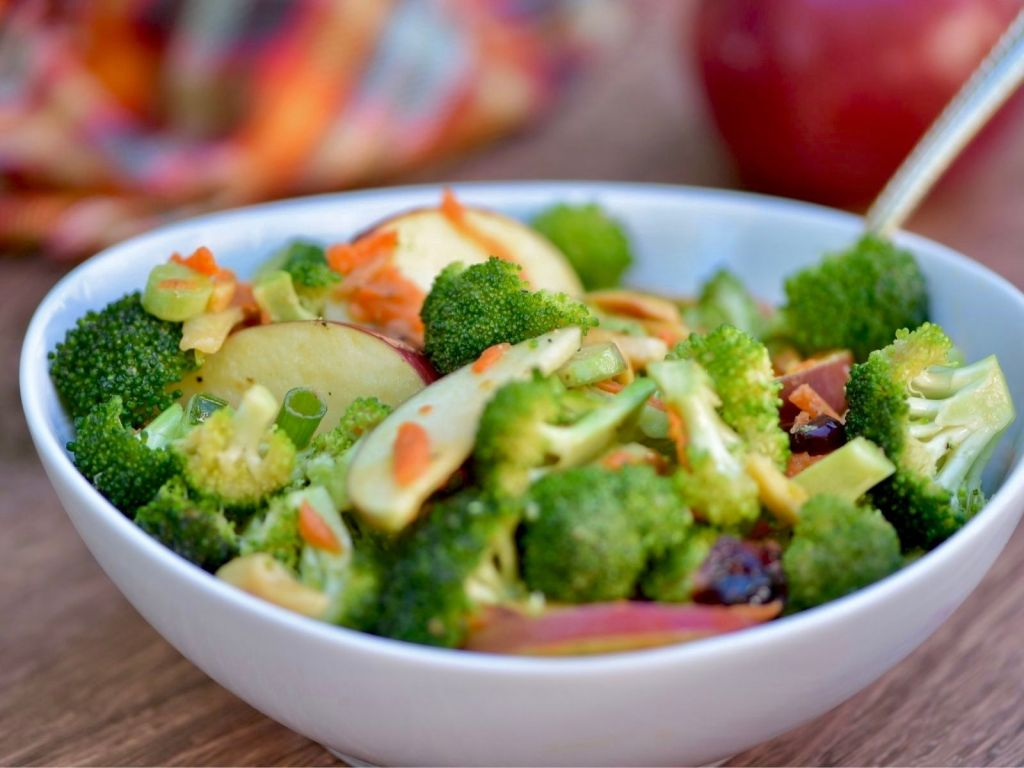 a white bowl of salad with broccoli florets, grated carrot, and apple slices with a plaid napkin and apple off to the side.