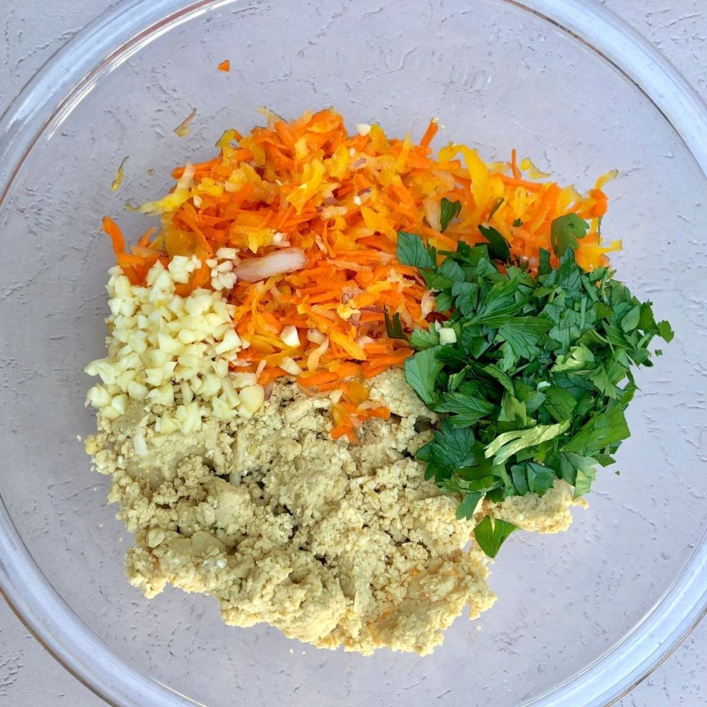 grated carrot, bell pepper, and onion, chopped parsley, and chickpea mixture in a glass bowl