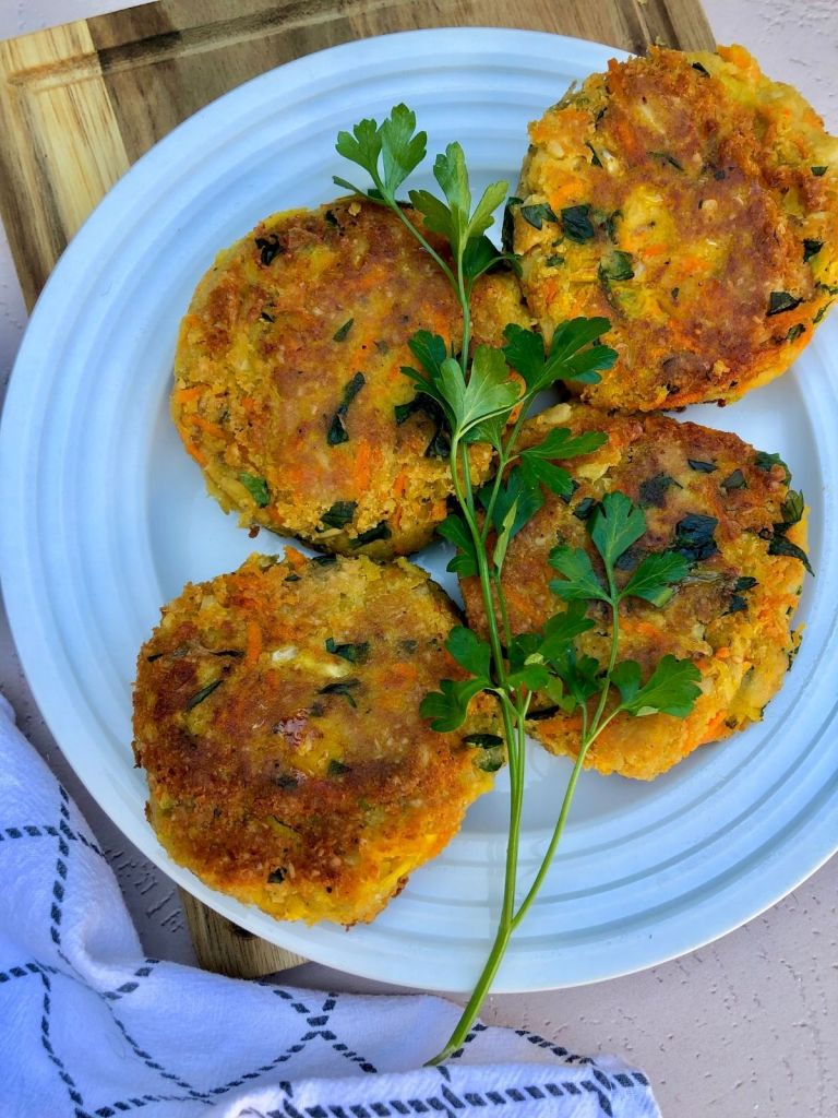 four chickpea patties on a white plate garnished with fresh parsley
