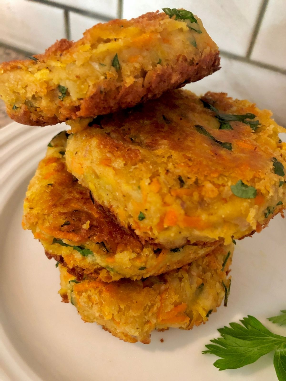 four chickpea patties piled high on a white plate garnished with fresh parsley, white subway tile in background