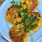 4 chickpea patties on a white plate garnished with fresh parsley