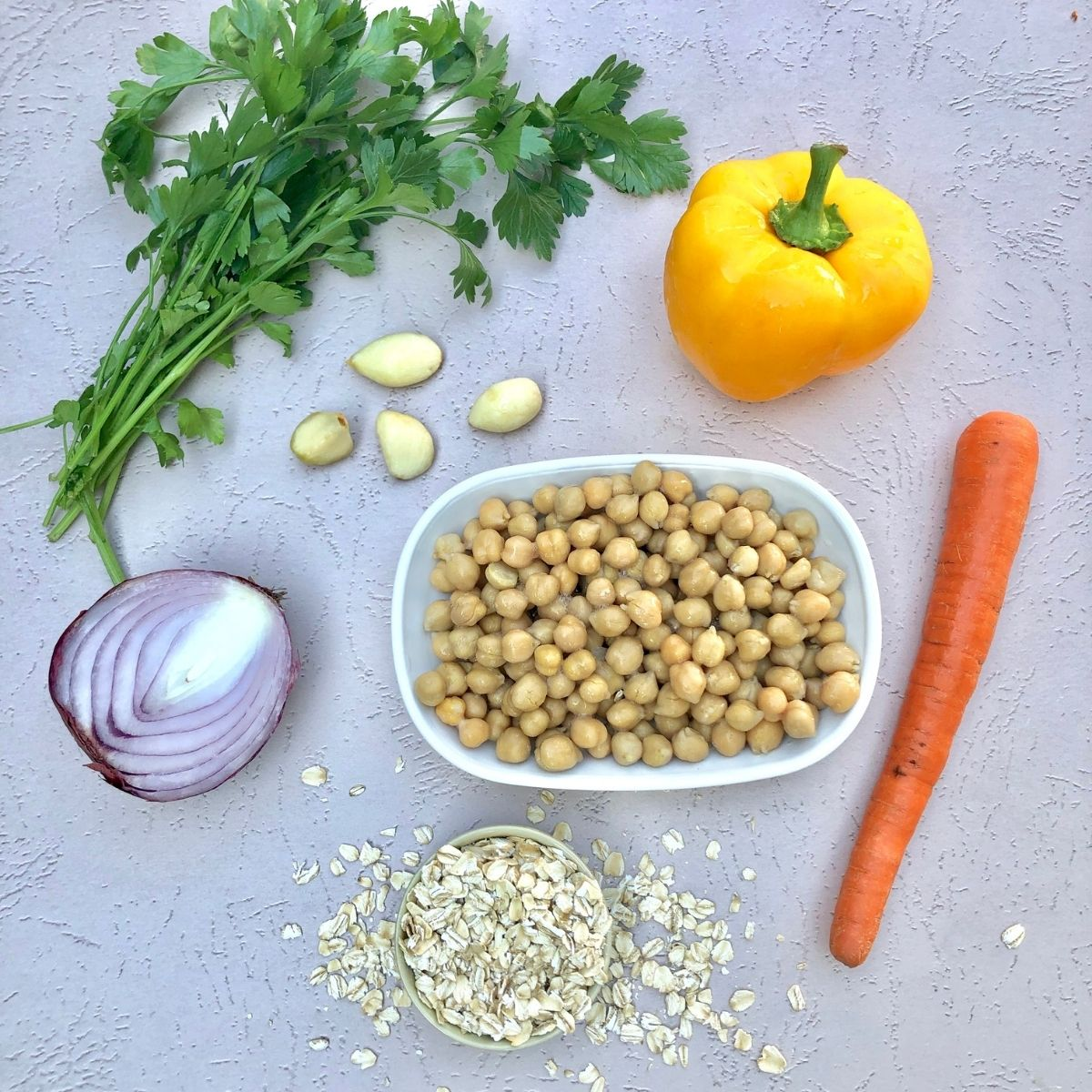 bunch of fresh parsley, yellow bell pepper, carrot, 1/2 red onion, 4 cloves garlic, and a small cup of oats on a pink backdrop