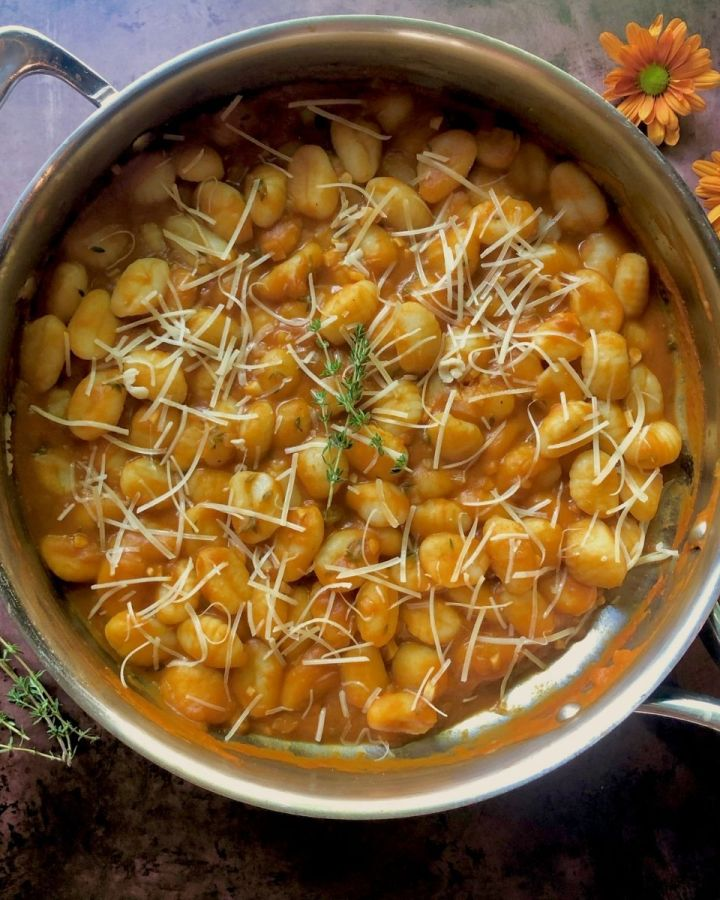 large skillet of pumpkin gnocchi garnished with parmesan cheese with 2 orange flowers off to side