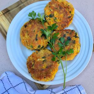 4 chickpea patties on a white plate on a wooden board n a pink backdrop garnished with parsley