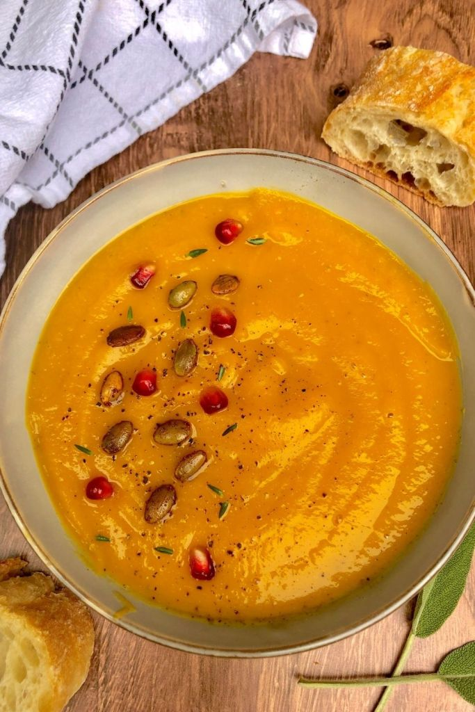 a bowl of butternut squash soup garnished with pomegranate and pumpkin seeds with crusty bread off to side